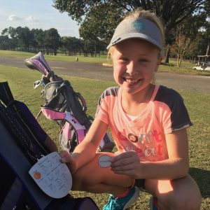 Junior Golfer showing off newly earned skill objective