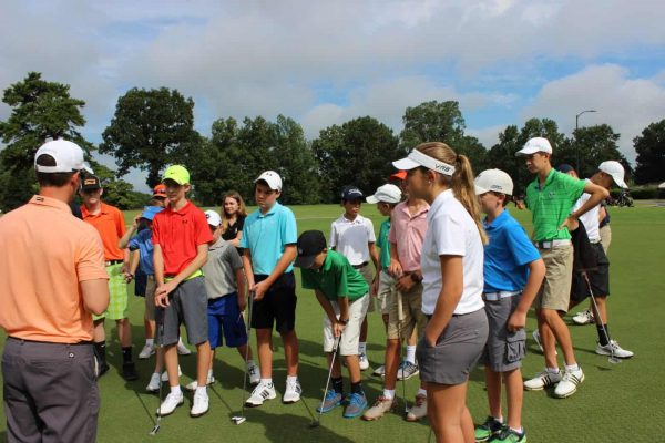 Students on the putting green listening to the coach go over the putting skill education during class