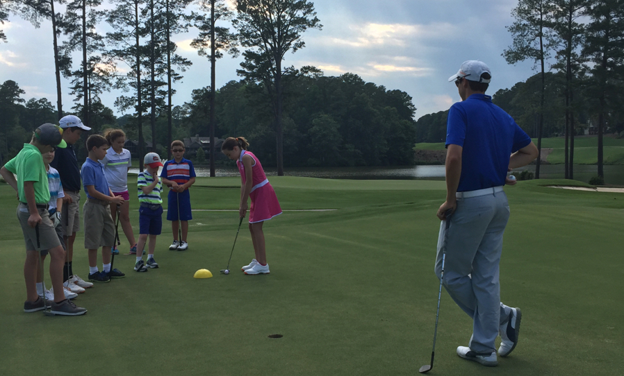 Coach watching as students practice their putting