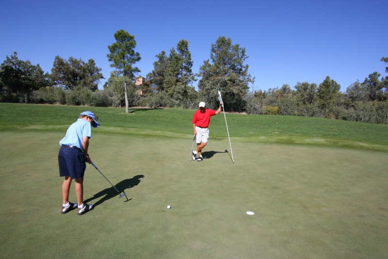Junior golfer hitting a putt as his father watches