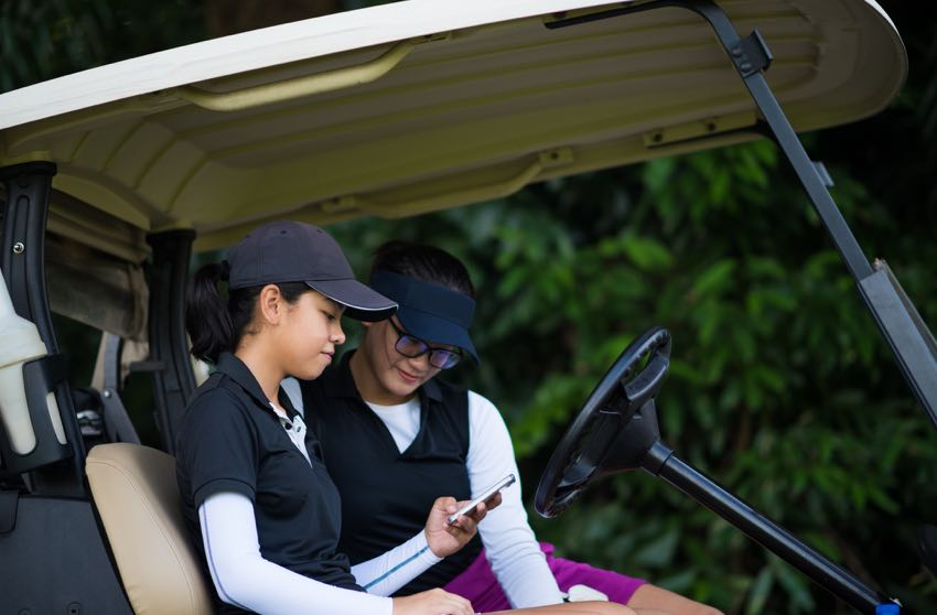 Mother and daughter playing golf entering their scores in the Op 36 app