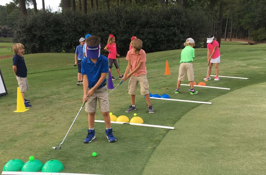 A class of junior golfers training their putting