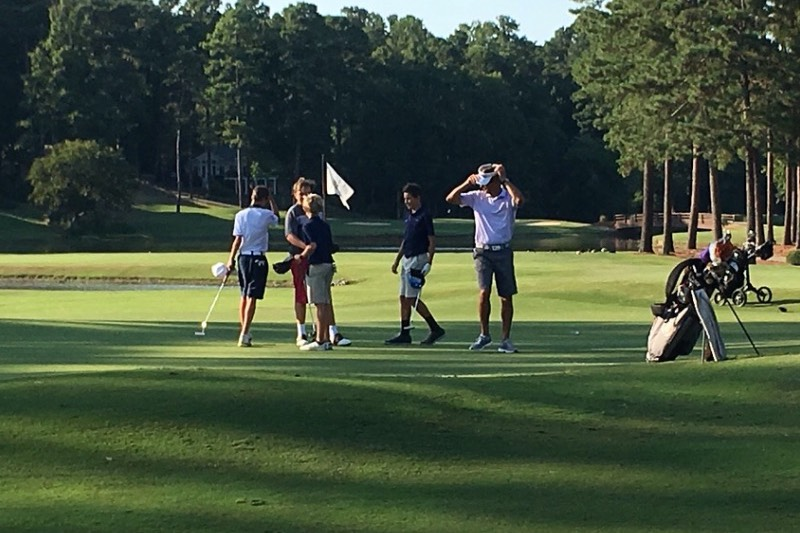 Group of junior golfers shaking hands after their round