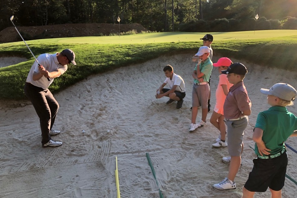 Op 36 coach demonstrating how to hit a sand shot