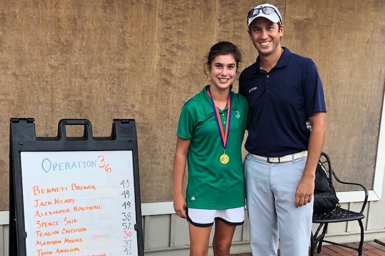Junior golfer standing beside her coach after winning a tournament