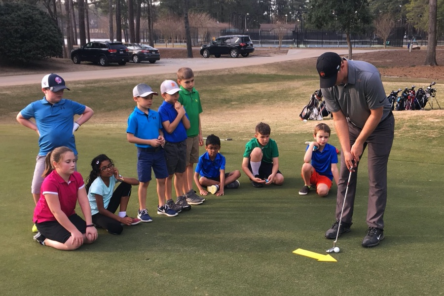 Op 36 coach demonstrating how to aim the putter