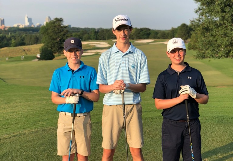 3 competitive junior golfers getting ready to play in an event