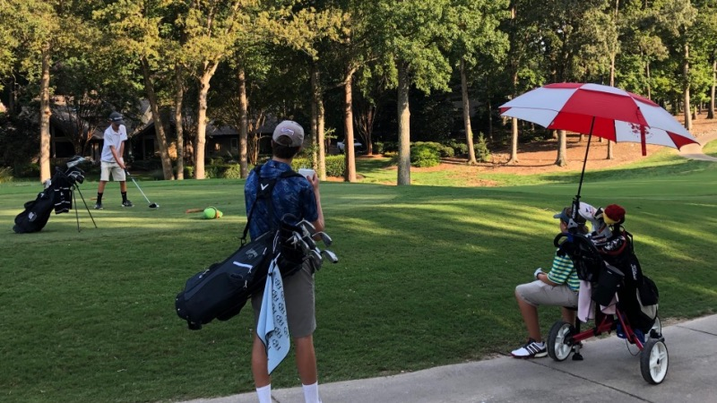 Two junior golfers watching their playing partner tee off