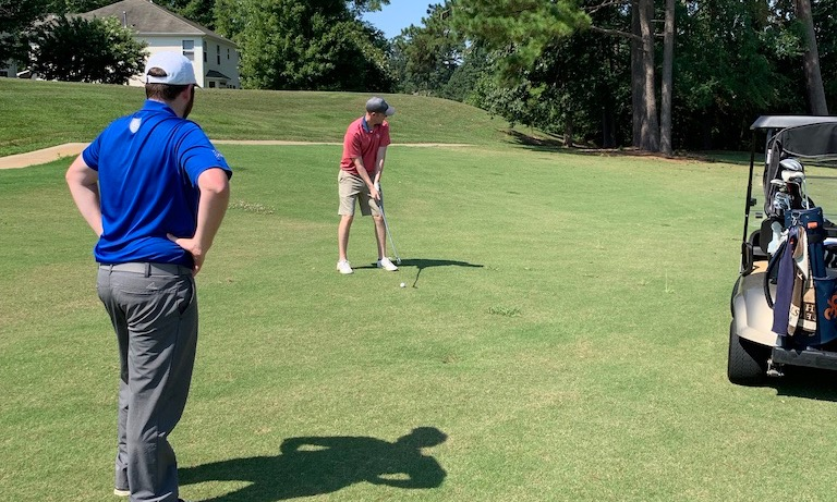 Op 36 golf coach watching student during playing lesson