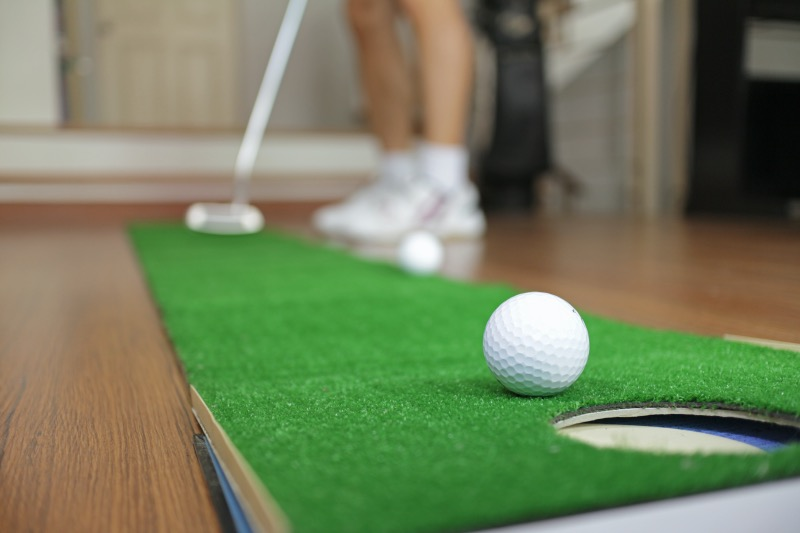Student practicing on putting mat at home