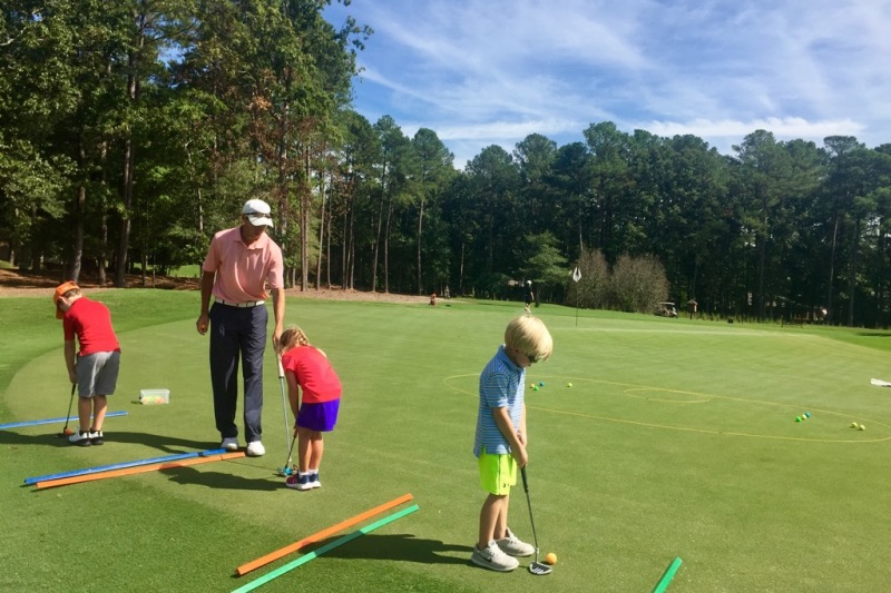 Op 36 coach working with young student on putting