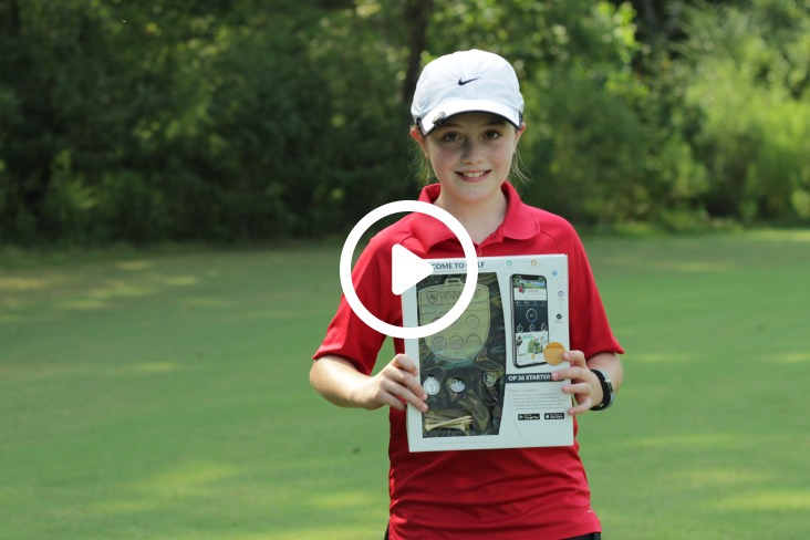Junior golfer holding up her Op 36 Starter Kit