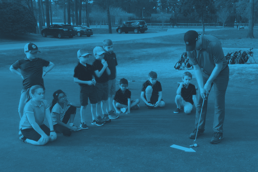 Op 36 coach demonstrating the putting skill to students in class
