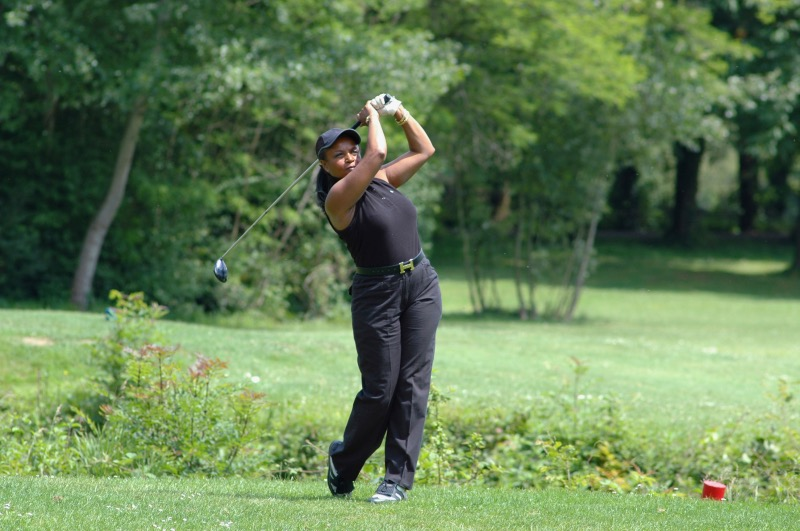 Female golfer teeing off