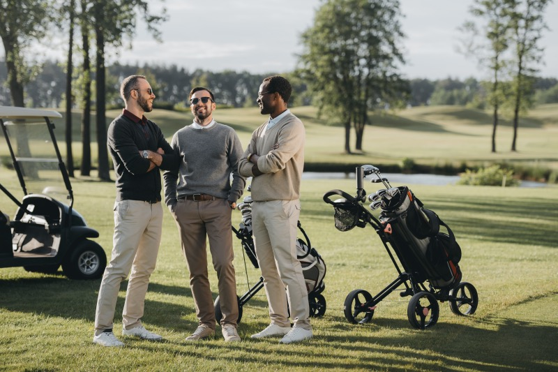 golfers with golf clubs talking and spending time together on golf course